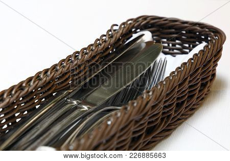 Close Up Metal Dining Utensils, Forks And Knives, In Wooden Basket Container On White Tablecloth, Hi