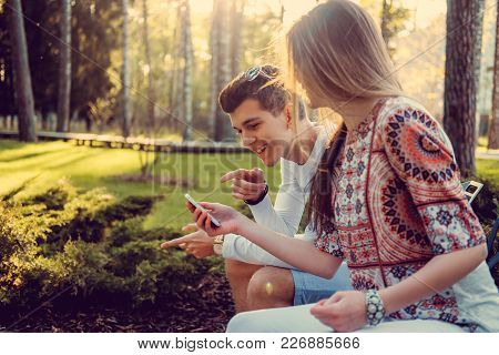 Young Attractive Couple Sitting On A Bench In A Park And Using Smartphone.