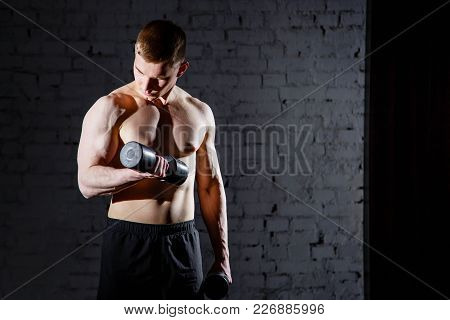 Handsome Young Man Doing Exercises For The Biceps Against A Brick Wall