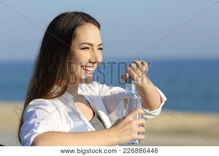 Casual Woman Opening A Water Bottle Sitting On A Bench On The Beach