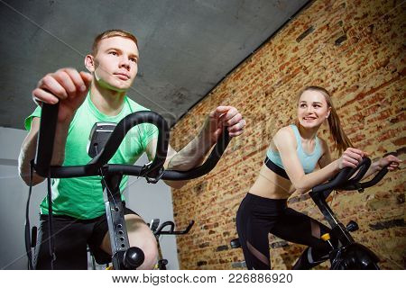 Young Man And Woman Biking In The Gym, Exercising Legs Doing Cardio Workout Cycling Bikes. Two Peopl