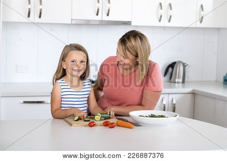 Young Attractive Woman Cooking Together With Her Sweet Beautiful Blond Little 6 Or 7 Years Old Daugh
