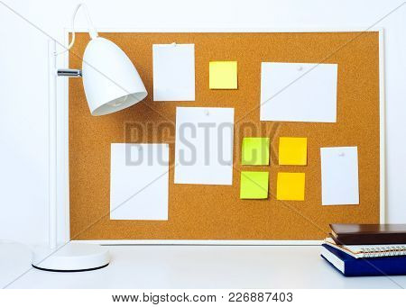 Framed Cork Notice Board With Various Paper Notes And Stickers. Lamp And Books On The Foreground