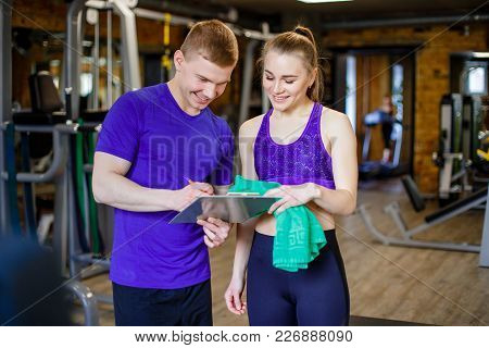 Shot Of A Personal Trainer Helping A Gym Member With Her Exercise Plan. Trainer Goes Through Fitness