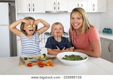 Young Attractive Woman Cooking Together With Little 3 And 7 Years Old Son And Daughter Playing Happy