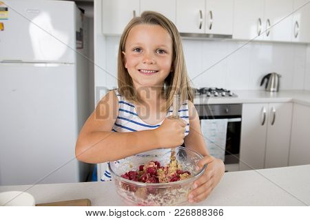 Young Beautiful And Adorable Girl 6 Or 7 Years Old Cooking And Baking At Home Kitchen Preparing Stra