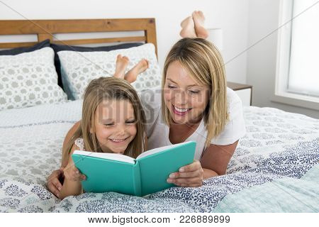 Young Blond Caucasian Woman Lying On Bed With Her Young Sweet  7 Years Old Daughter Reading Book Tog