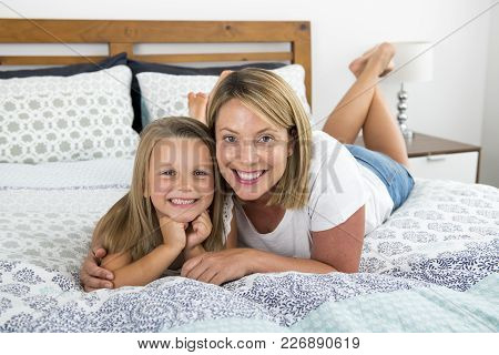 Young Blond Caucasian Woman Lying On Bed Together With Her Young Sweet And Adorable 7 Years Old Daug