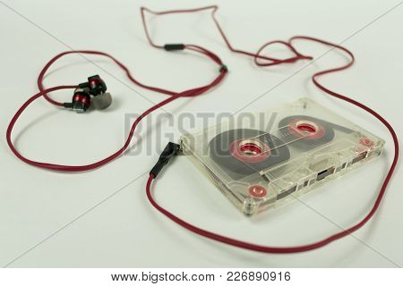 Transparent Audiocassette Surrounded By A Cord Of Headphones In The Shape Of A Heart On A White Back