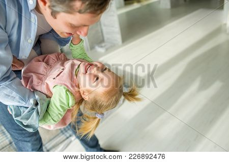 The Father Plays With The Little Daughter. The Child Laughs From Pleasure.