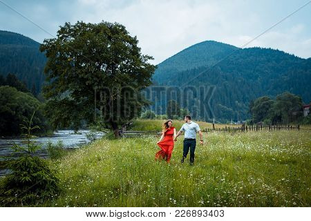 Portrait Of The Beautiful Happy Couple Holding Hands And Walking Along Daisy Meadow Near The River I