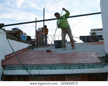 Alora, Spain - November 23, 2011: Men Painting Red Waterproof Paint On Concrete Roof Before Laying T