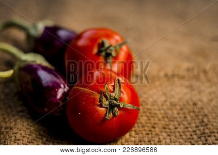 Close Up Of Vegetables For A Spicy Indian Lunch I.e Egg Plant,solanum Melongena & Tomato,solanum Lyc