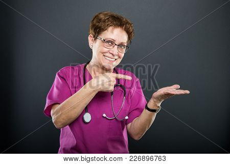 Portrait Of Senior Lady Doctor Pointing Copyspace Area