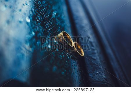 Gold Wedding Rings On The Car Window