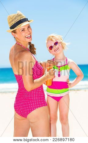 Blue Sea, White Sand Paradise. Smiling Young Mother And Daughter In Colorful Swimwear On The Beach A