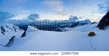 Tent In The Snow Mountains At The Top Of Hill At Sunset In Altaj, Russia  At The Summer