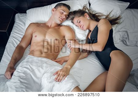 Attractive Shirtless Male And Sexy Female In A Black Underwear Relaxing On A Bed In Modern Apartment
