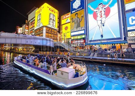 Osaka, Japan - April 29, 2017: Touristic Boat In Dotonbori Canal And Famous Glico Running Man Sign I