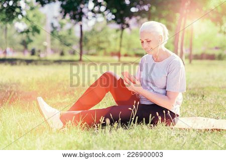 Relax For Soul. Full Length Of Cheerful Elderly Woman Sitting On The Ground Pad While Using Mobile P