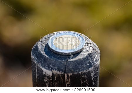 A Two Euro Coin Lies On A Fence Post.