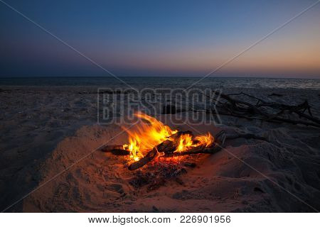 Cooking Coffee While Traveling On The Wild Seashore -  Small Kettle Stands Next To A Blazing Bonfire