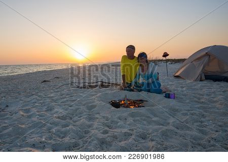 Couple Of Romantic Travelers Sit Next To Burning Bonfire On The Beach, Admire Flame And Going To Dri