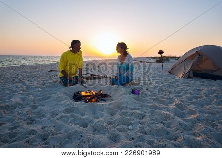 Happy Adventurers Sit Next To Burning Bonfire On The Beach, Admire Flame And Going To Drink Coffee O