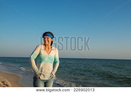 Joyful Woman Traveler, With Hair Flying In The Wind, Walks Along The Sea Coast, Enjoys Life And Smil