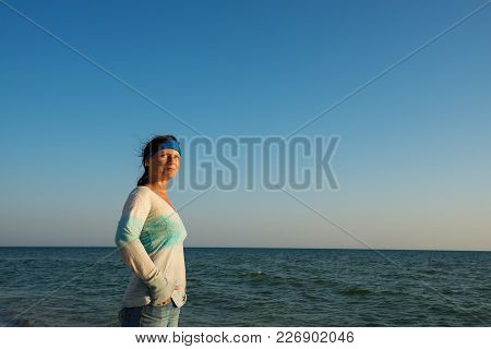 Strong Woman Traveler, With Hair Flying In The Wind, Walks Along The Sea Coast, Enjoys Life And Smil