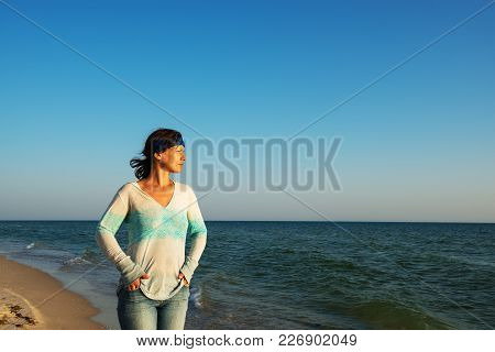 Strong Woman Traveler, With Hair Flying In The Wind, Walks Along The Sea Coast, Looks Into The Dista