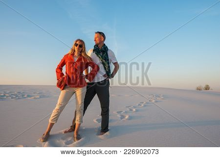 Romantic Couple Is Posing In The Desert Against A Blue Sky On A Sunny Evening, Smiling And Dreaming.