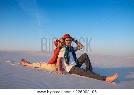 Joyful Couple Sitting, Back To Back, In The Desert Against A Blue Sky On A Sunny Evening, Laughing A