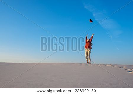Expressive Young Woman, Blonde Jumps, With Open Arms, In The Desert And Catches Her Flying Hat In Th