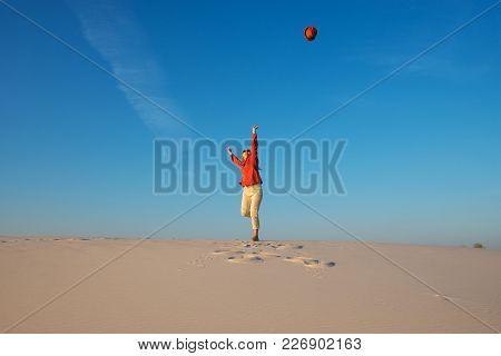 Joyful Young Woman, Blonde Walks In The Desert, Admires The Flight Of Her Hat In The Blue Sky, Dance