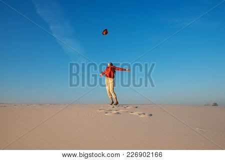 Expressive Young Woman, With Open Arms, Blonde Walks In The Desert And Admires The Flight Of Her Hat