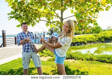 Laughing Parents With Small Daughter Are Playing And Having Fun In Park Against Background Of A Gree