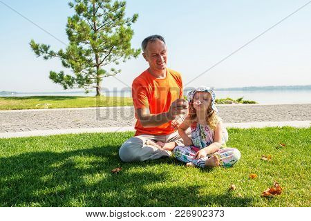 Smiling Father With A Small Daughter Relax On A Green Meadow Near The River On A Beautiful Sunny Day