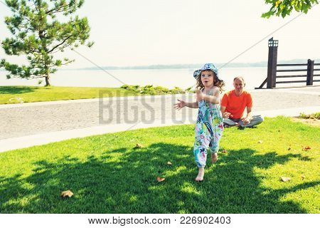 Joyful Small Daughter Plays With Her Father In The Park, She Runs Through Green Meadow Next To River