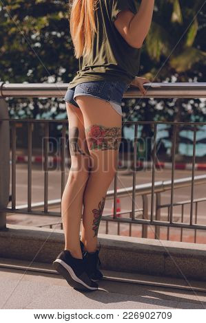 Cropped Shot Of Tattoed Young Woman In Shorts Outdoors