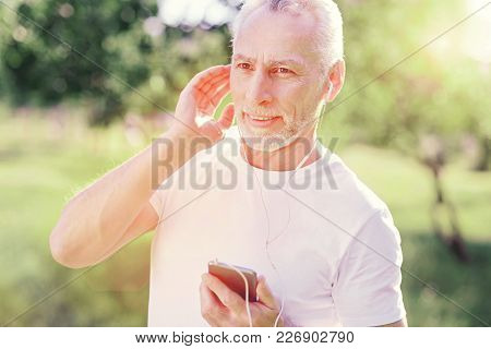 Familiar Song. Close Up Of Pleasant Man Being Attentive While Using Mobile Phone And Touching His He