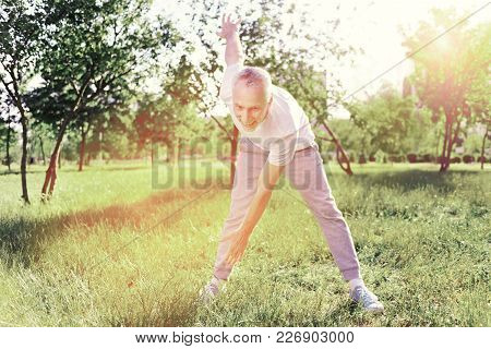 Ready For Exercises. Optimistic Elderly Man Doing Exercises In Fresh Air While Being Excited And Ple