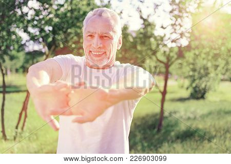 Becoming Healthier. Close Up Of Cheerful Man Keeping Hands In Front Of You While Standing And Expres