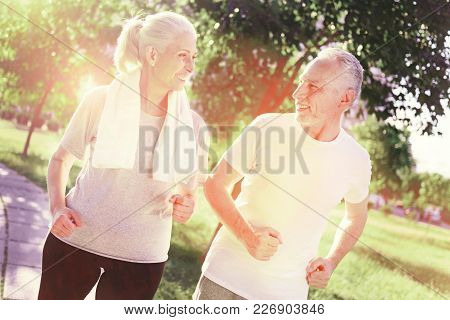 Expressive. Waist Up Positive Elderly Couple Walking Through The Park While Looking At Each Other Wi