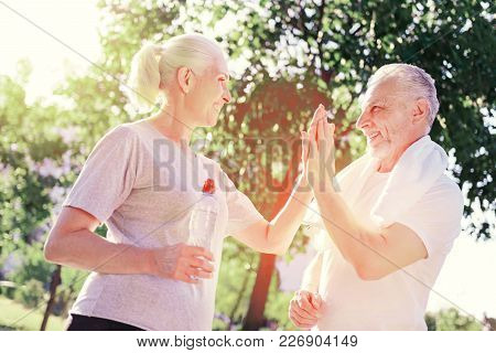 Great Mood. Waist Up Of Elderly Couple Standing In Front Of Each Other While Keeping Palms Together