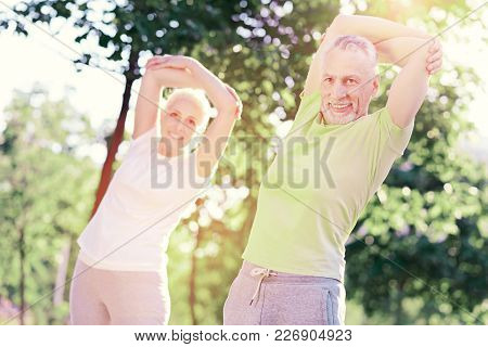Learning New Exercises. Waist Up Of Elderly People Keeping Hands Up While Expressing Delight Standin
