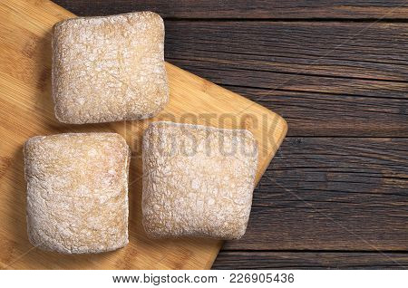 Loaves Of Ciabatta Bread On A Cutting Board On The Old Dark Wooden Table, Top View With Space For Te