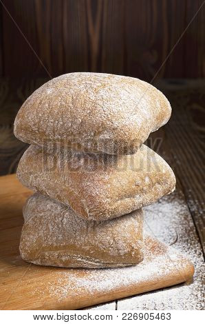 Stack Of Small Ciabatta Bread On A Cutting Board On The Dark Wooden Table