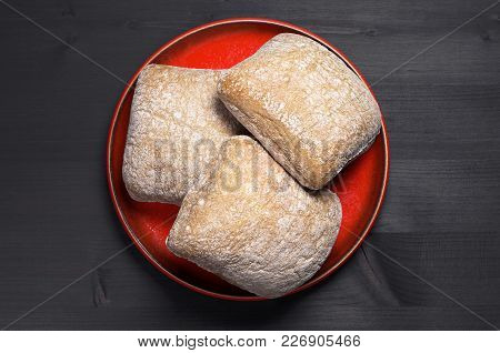 Small Loaves Of Ciabatta Bread In Red Plate On Black Wooden Background, Top View