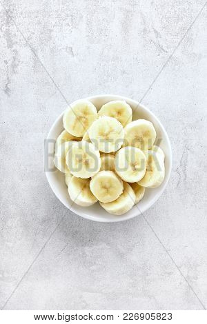 Bowl With Peeled Sliced Banana On Stone Background With Copy Space. Healthy Vegetarian Vegan Food. T